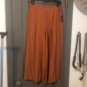 Orangish colored pants with side splits